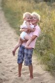 Brother with his baby sister on the beach — Stock Photo