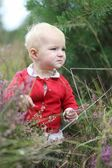 Baby girl walks in heather field — Stock Photo