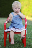 Baby girl sitting on chair outdoors — Stock Photo