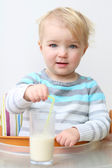 Girl drinking milk from the glass with straw — Stock Photo