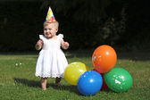 Baby girl next to colorful balloons — Stock Photo