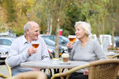 Couple of seniors enjoying glass of cold beer — Stock Photo