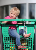 Baby sitting in a shopping trolley at a hypermarket — Stok fotoğraf