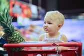 Baby girl sitting in red shopping cart at supermarket — Stock Photo