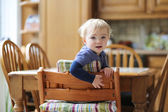 Girl sitting in the kitchen in high chair — Stock Photo
