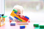 Girl playing peek-a-boo hiding behind plastic blocks — Stock Photo