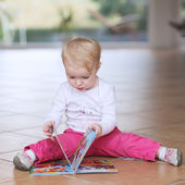 Baby girl reading book sitting indoors — Stock Photo