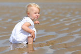 Baby girl sitting on a beach — Stock Photo