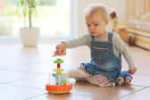 Baby girl plays with toys on floor — Stock Photo