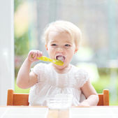 Girl eating delicious yogurt — Stock Photo