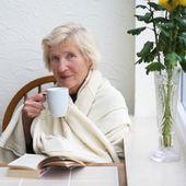 Senior woman drinking delicious coffee — Stock Photo