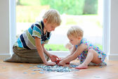Girl playing puzzles with her teenager brother — Stock Photo