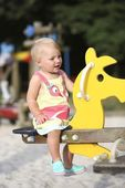 Girl swinging on a yellow spring horse — Stock Photo