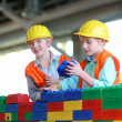 Brothers building a house with big plastic construction bricks — Stock Photo