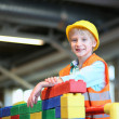 Boy building a house with big plastic construction bricks — Stock Photo #42871053