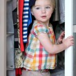 Toddler girl playing hide and seek in mother's wardrobe — Stock Photo