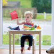 Toddler girl making paper planes — Stock Photo