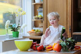 Girl eating cucumber preparing healthy vegetables salad — Stock Photo