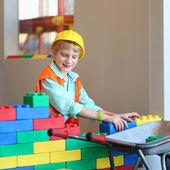 Chlapec stavby domu s velkou plastovou stavební cihly — Stock fotografie