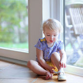 Toddler girl putting on her shoe sitting on floor — Stock Photo