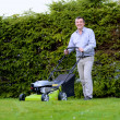 Man mowing the lawn in the backyard — Stock Photo