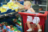 Girl sitting in red shopping cart in supermarket — Stock Photo