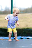 Girl jumping on trampoline in the garden — Stock Photo