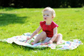 Girl sitting on the blanket in the garden — Stock Photo