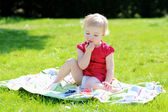 Child sitting on the blanket in the garden — Stock Photo