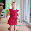 Lovely toddler girl walking indoors in mom's red shoes — Stock Photo