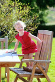 Happy toddler girl playing in the garden sitting at wooden picnic table — Stock Photo