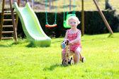 Cute blonde toddler girl riding wooden horse in summer garden — Stock Photo