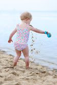 Happy little girl in spotty swimsuit playing on sandy beach — Stock Photo