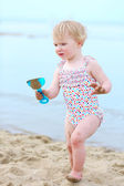 Happy toddler girl playing on the beach — Stock Photo