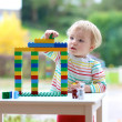 Happy toddler girl playing with colorful blocks indoors — Stok fotoğraf #44119571