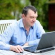 Businessman working from home sitting with laptop outside in the garden — Stock Photo #44119619