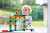 Happy toddler girl playing with colorful blocks indoors — Stock Photo