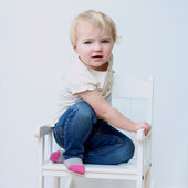 Portrait of happy little child in casual clothes posing indoors on a white rocking chair — Stock Photo