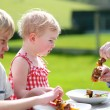 Father putting meat for children, cute toddler girl and funny teenager boy. — Stock Photo