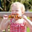Toddler girl eating delicious meat — Stock Photo