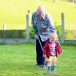 Man working in the garden with granddaughter — Stock Photo #44611887