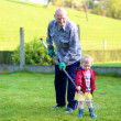 Man working in the garden with granddaughter — Stock Photo #44611893
