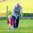 Man working in the garden with granddaughter — Stock Photo