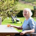 Happy senior woman relaxing in summer garden — Stock Photo #45453531