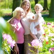 Three generations in floral park — Stock Photo