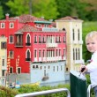 Little girl looks at miniature installations at amusement park — Stock Photo