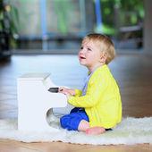Küçük kız içeride oyuncak piyano — Stok fotoğraf