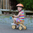 Happy little child in safety helmet riding wooden tricycle — Stock Photo #46835259