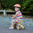 Happy little child in safety helmet riding wooden tricycle — Stock Photo #46835275