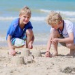 Two happy boys building sand castles on the beach — Stok fotoğraf